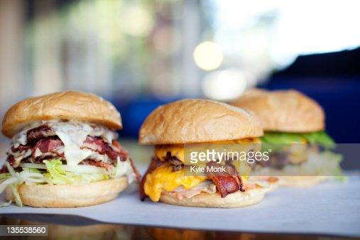 Various indulgent cheeseburgers in diner : Stock Photo