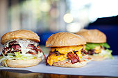 Various indulgent cheeseburgers in diner