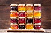 various jars of fruit jam on wooden table