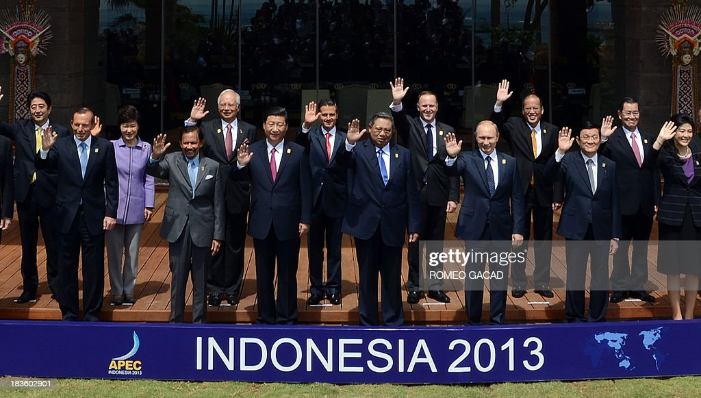 Various leaders wave for the traditional 'leaders' family photo' at the Asia-Pacific Economic Cooperation (APEC) Summit in Nusa Dua on the Indonesian resort island of Bali on October 8, 2013. Pictured are (front row L to R) Australia's Prime Minister Tony Abbott, Brunei's Sultan Hassanal Bolkiah, China's President Xi Jinping, Indonesia's President Susilo Bambang Yudhoyono, Russian President Vladimir Putin, Vietnamese Prime Minister Nguyen Tan Dung, Thailand's Prime Minister Yingluck Shinawatra, and (second row L to R) Japan's Prime Minister Shinzo Abe, South Korean President Park Geun-Hye, Malaysia's Prime Minister Najib Razak, Mexico's President Enrique Pena Nieto, New Zealand Prime Minister John Key, Philippine President Benigno Aquino and Vincent Siew, Taiwan's former vice president.