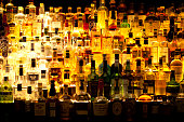 Various liquor bottles sitting behind bar, backlit