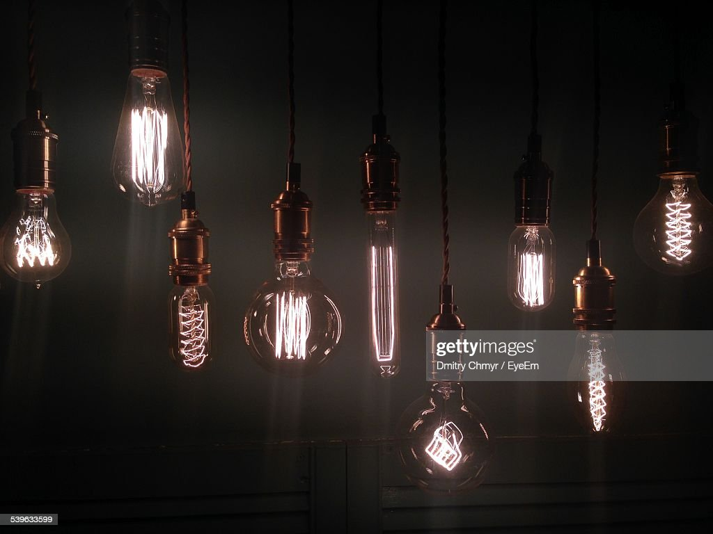 Various Lit Light Bulbs Hanging Against Sky At Night