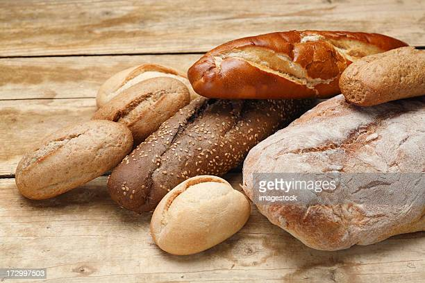 Various loaves of bread piled on a wooden table