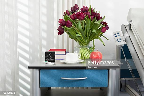Various objects on a bedside table in a hospital ward