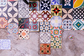 Various of type and color floor square tiles with concrete floor.