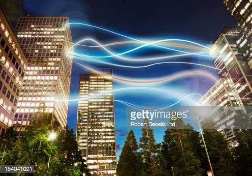 various offices connected via light trails in city : Stock Photo