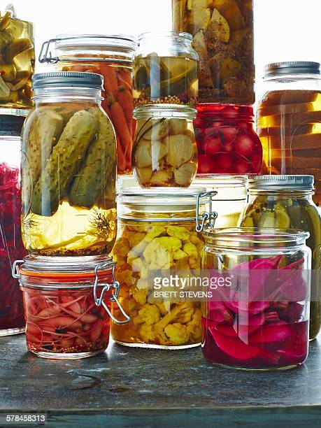 Various pickles in glass jars, close-up