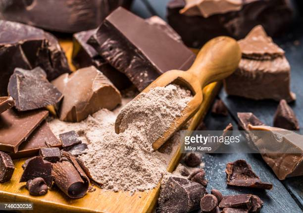 Various pieces of chocolate around wooden scoop with chocolate powder