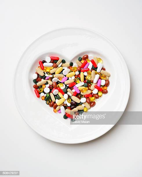 Various pills in a heart shaped bowl