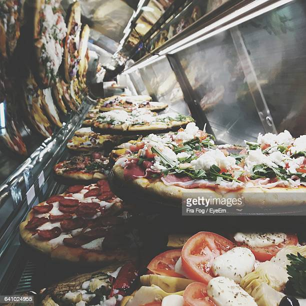 Various Pizza Displayed In Cabinet At Store