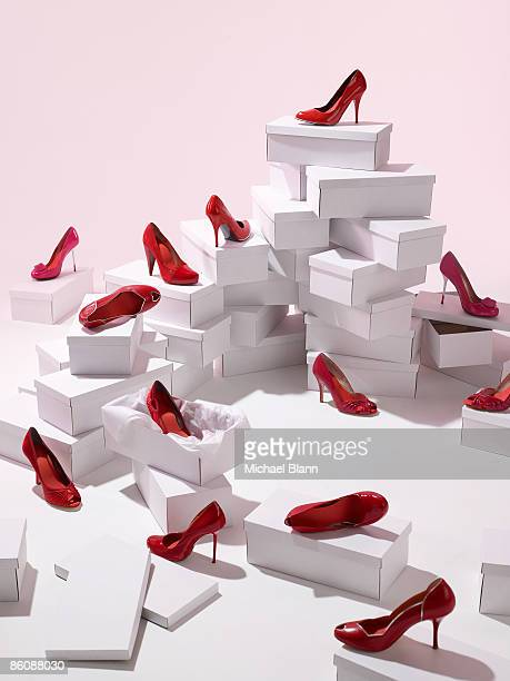 Various red shoes on top of shoe boxes