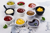 Various sauces and dips in porclean bowls on white stone background. Copy space