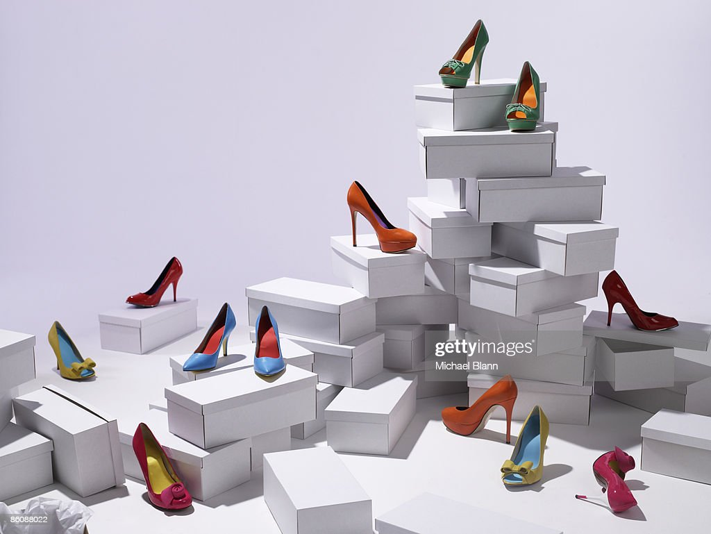Various shoes piled on shoe boxes : Stock Photo