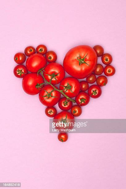 Various sizes of tomatoes arranged into the shape of a heart