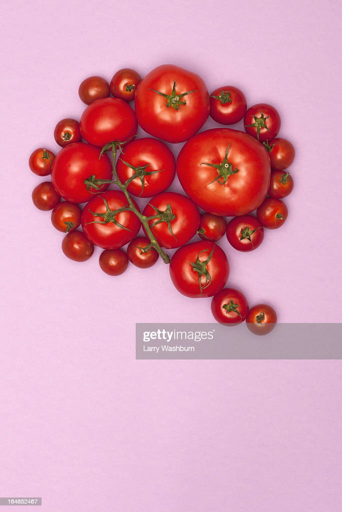 Various sizes of tomatoes arranged into the shape of a speech bubble : Stock Photo