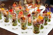 Various snacks in shot glasses on table
