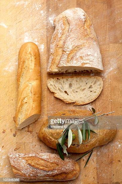 Assorted white bread on wooden board, close-up