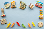 colorful paper ships and  various souvenir magnets from several world country arranged on the blue background