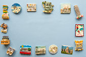 various fridge magnets arranged on the blue background, travel concept