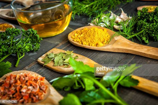 Various spice on wooden spoons with herbs
