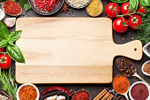 Various spices, herbs and cutting board on stone table. Top view with space for your text