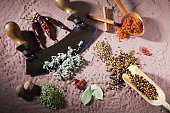 Various spices with a mincing knife on a sandstone base
