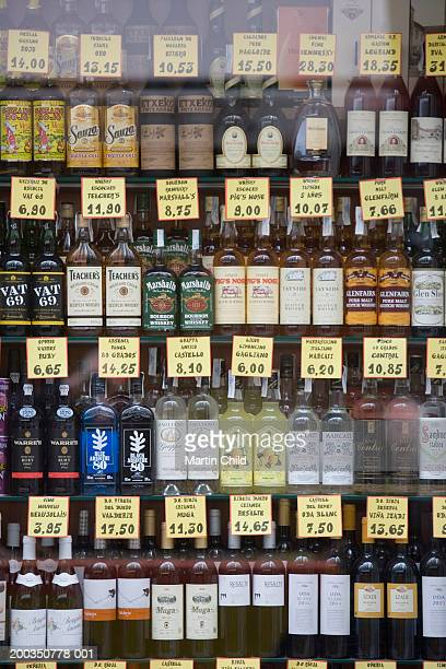 Various spirits and liqueurs in shop window, view through glass