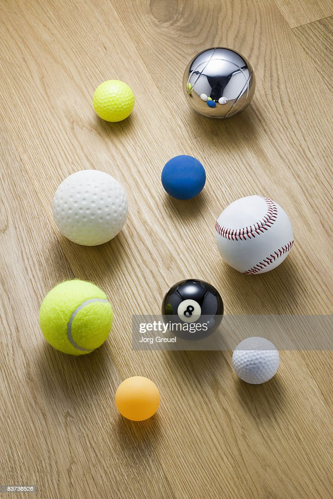Various sports balls on wooden floor