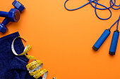 various sports equipment, measuring tape and towel isolated on orange