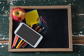 Various stationery with apple and mobile phone on table