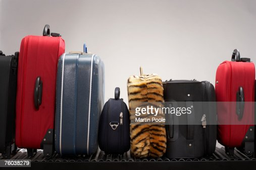Various suitcases on conveyor belt : Stock Photo
