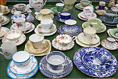Various tea cups and saucers on market stall, close-up