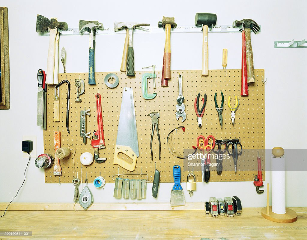 Various tools hanging on grid above workbench : Stock Photo