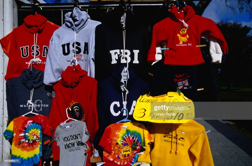 Various tops and t-shirts with USA National Security logos displayed for sale.