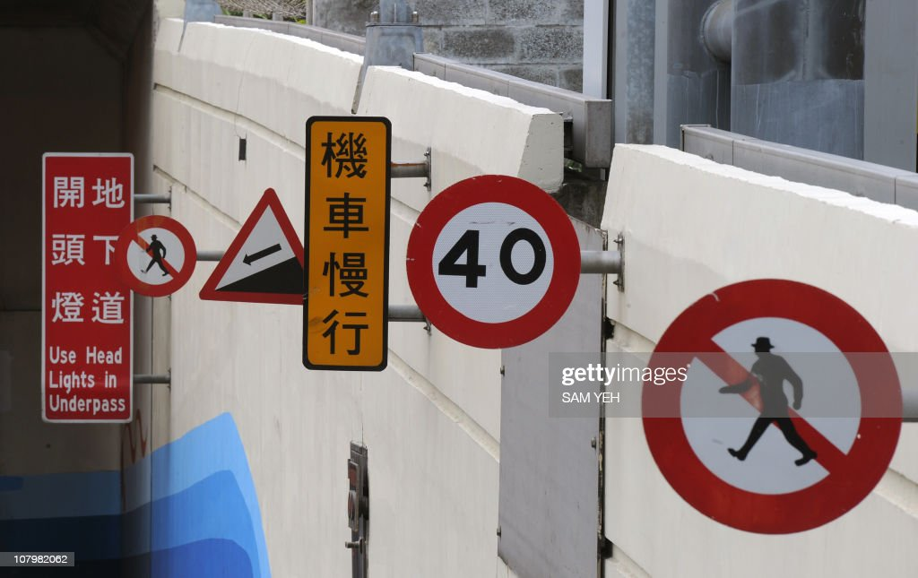 Various traffic signs are shown at the entrance of a tunnel in Taipei on January 5, 2011. AFP PHOTO / Sam YEH