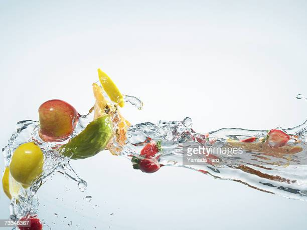 Various tropical and citrus fruit pieces being splashed with water