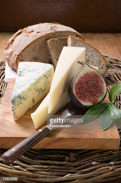 Various types of cheese, bread and half a fig