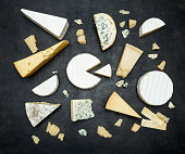 Various types of cheese - parmesan, brie, roquefort, cheddar on concrete background or table