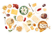 An assortment of various types of cheese with wine, and grapes, shot from above on a white background