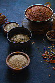 Various types of rice and grains with spices on blue background. Brown rice and mixed wild rice.