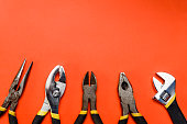 Various Used Pliers Tools on a orange textured background with space for text