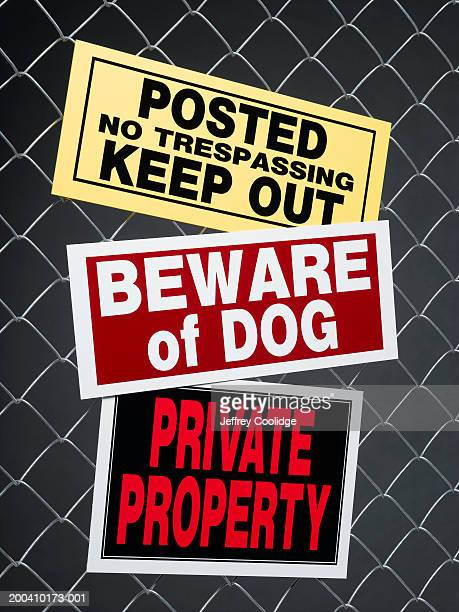 Various warning signs on chain link fence