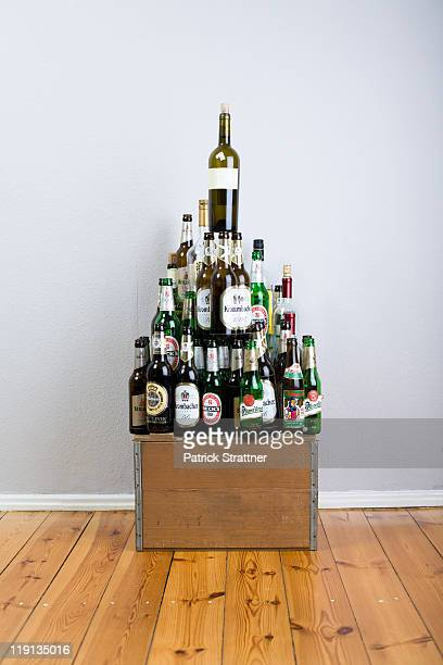 Various wine and beer bottles stacked into a pyramid shape