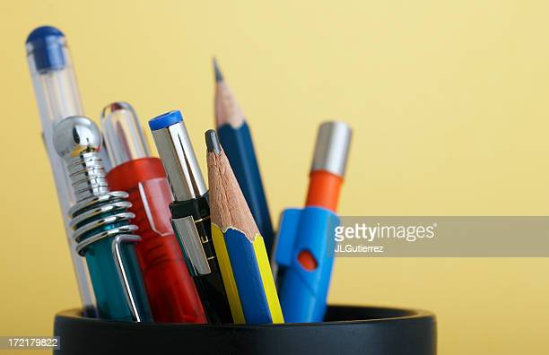 Various writing utensils in a round holder