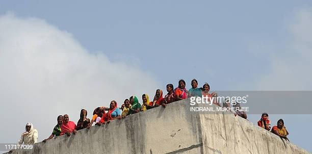 VarkariHindu pilgrims look on from a guesthouse terrace as they await the start of the annual pilgrimage at the temple of Saint Dnyaneshwar at Alandi...