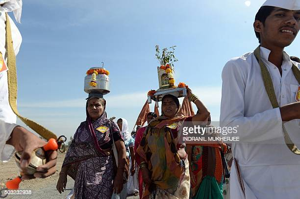 Varkari's Indian Hindu pilgrims who follow a religious movement within the spiritual tradition of Hinduism sing songs as they arrive to take part in...