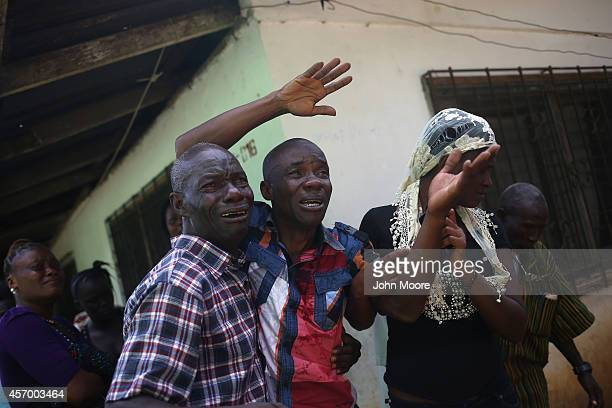 Varney Jonson grieves as an Ebola burial team takes away the body of his wife Nama Fambule for cremation on October 10 2014 in Monrovia Liberia He...
