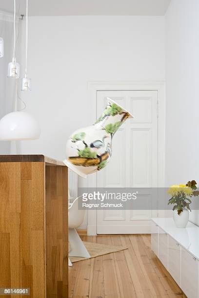 A vase falling from a counter