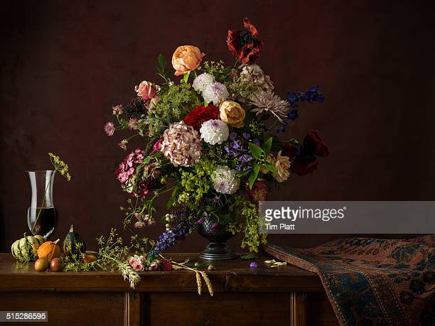 Vase of cut flowers on a wooden table.