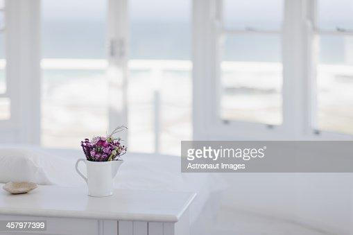 Vase of flowers on desk in bedroom overlooking ocean
